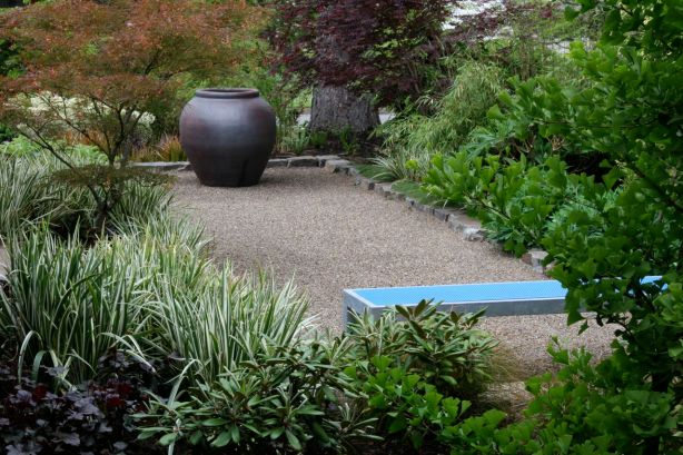 A custom metal bench anchors one end of this simple, pea gravel terrace.